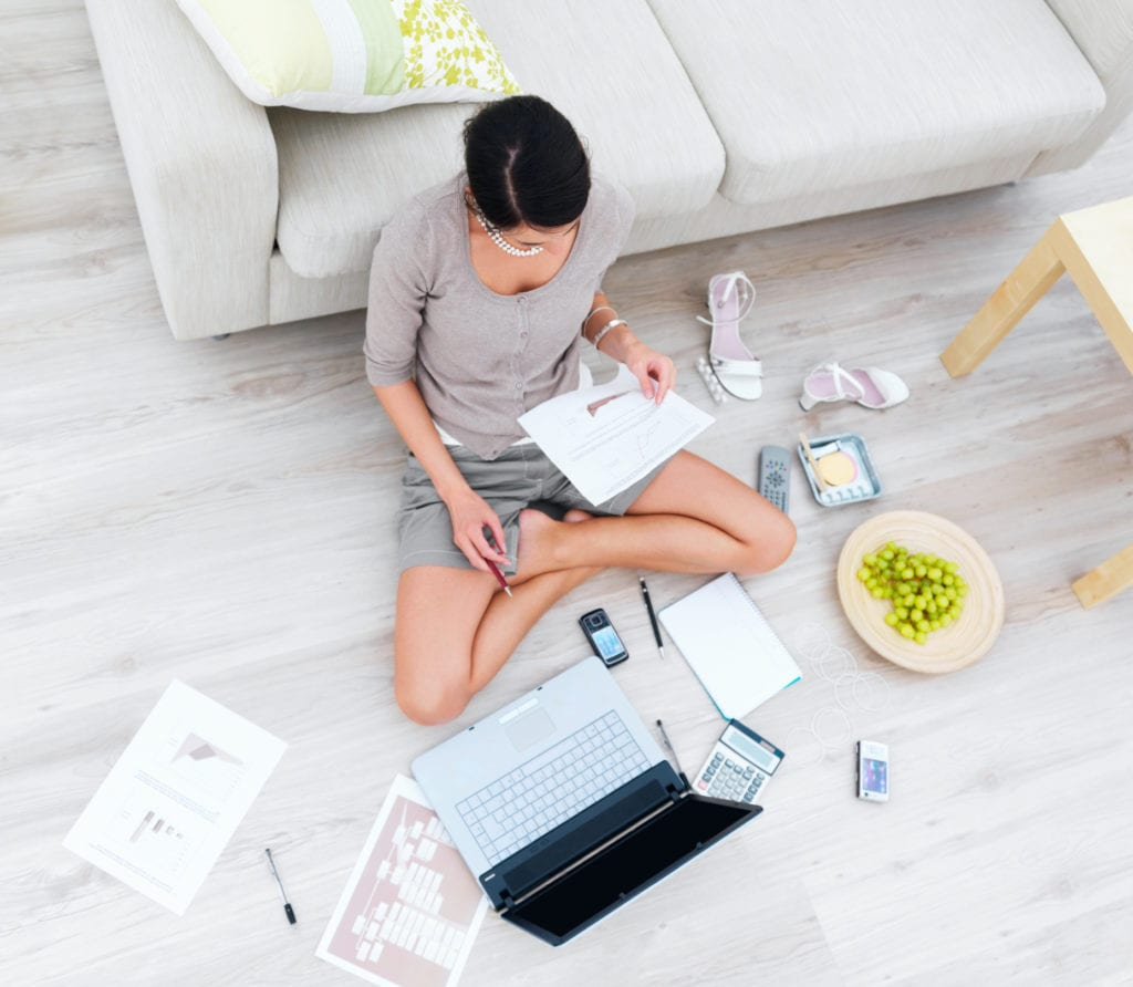 High angle view of businesswoman sitting in house with laptop and documents