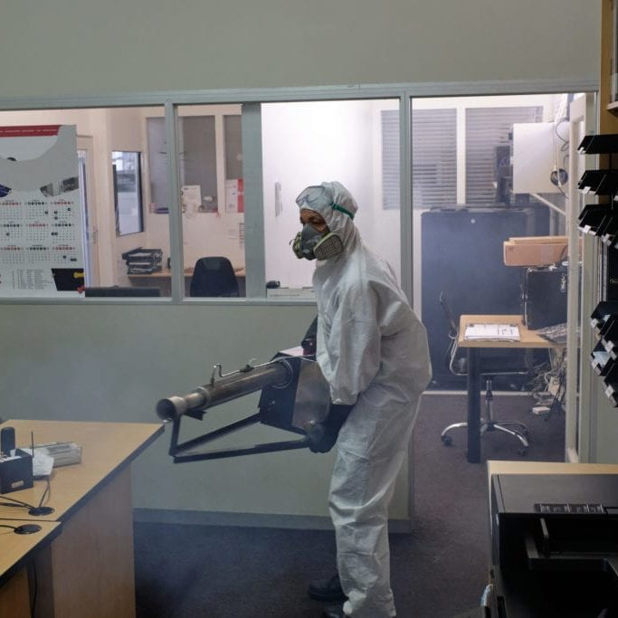 A man dressed in full protective gear uses an industrial fogging machine to spray and disinfect an entire office space. Sanitization/fogging to help stop the spread of the Coronavirus, Cape Town.