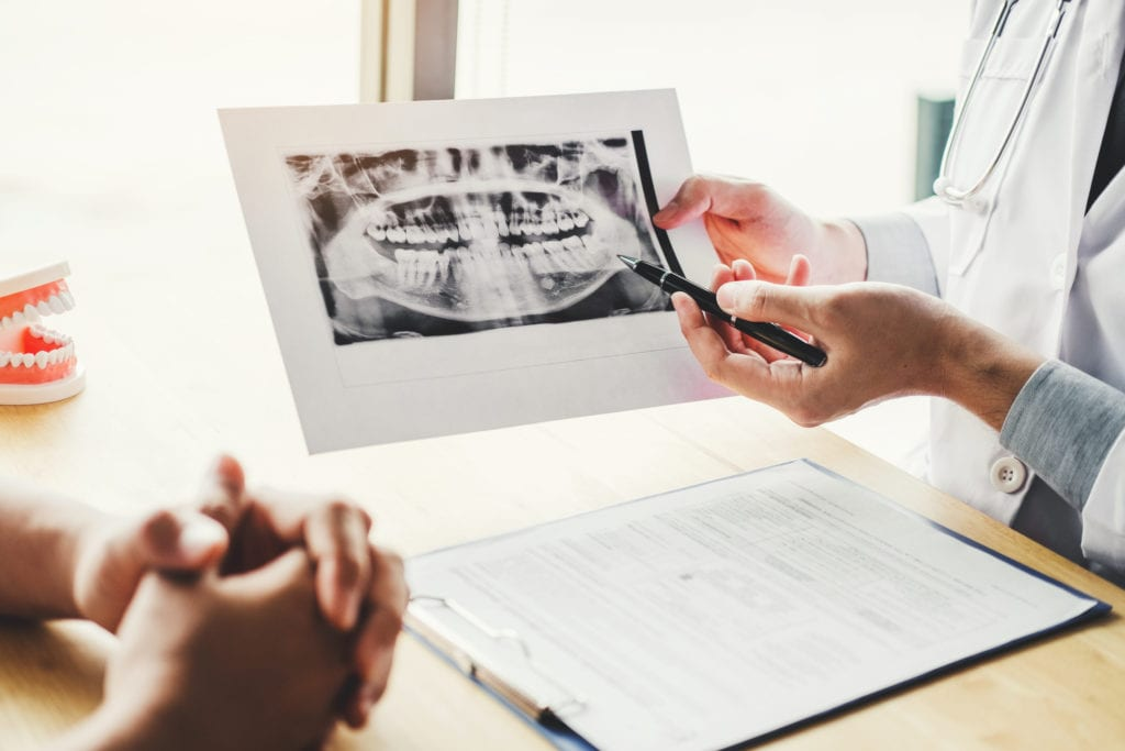 Dentist talking to male patient and presenting results on Dental x-ray film About the problem of the patient in dental office