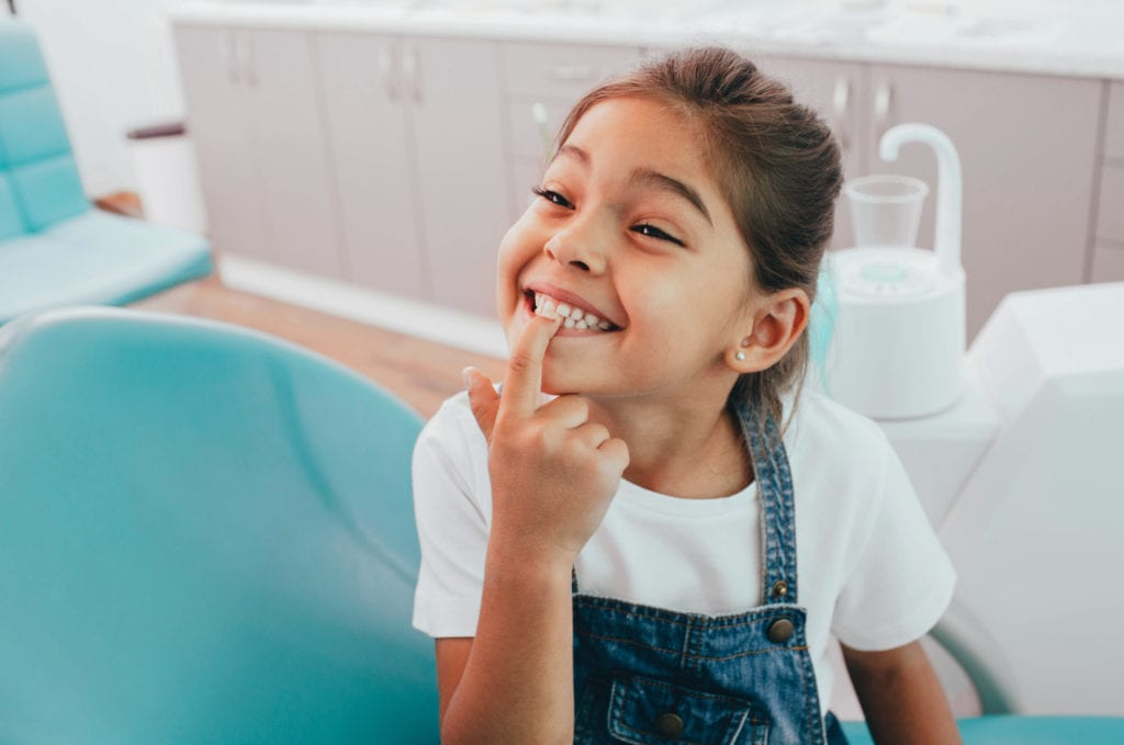 Young child smiling and pointing at tooth