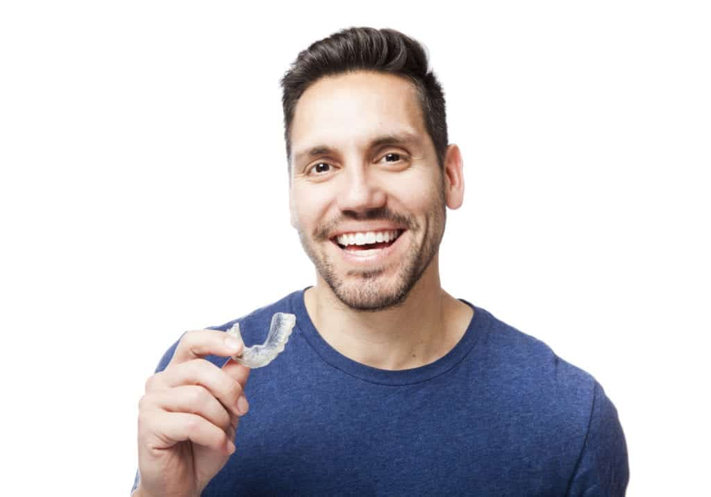 Man holding Invisalign aligners
