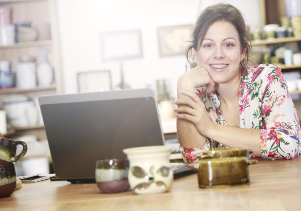 Smiling woman with ceramic braces in her studio with a computer