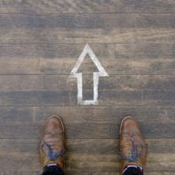 The way forward: A man standing in front of arrow sign on wooden floor
