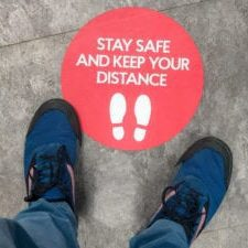A sign on the floor of a shop, advising customers regarding sociala distancing guidelines.