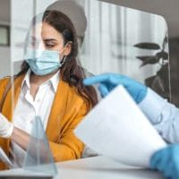 Bank teller explaining paperwork to customer at bank counter wearing protective gloves and face mask. Office with acrylic glass partition on desk. Acrylic glass wall - protection against coughs and spitting, protection against viruses.