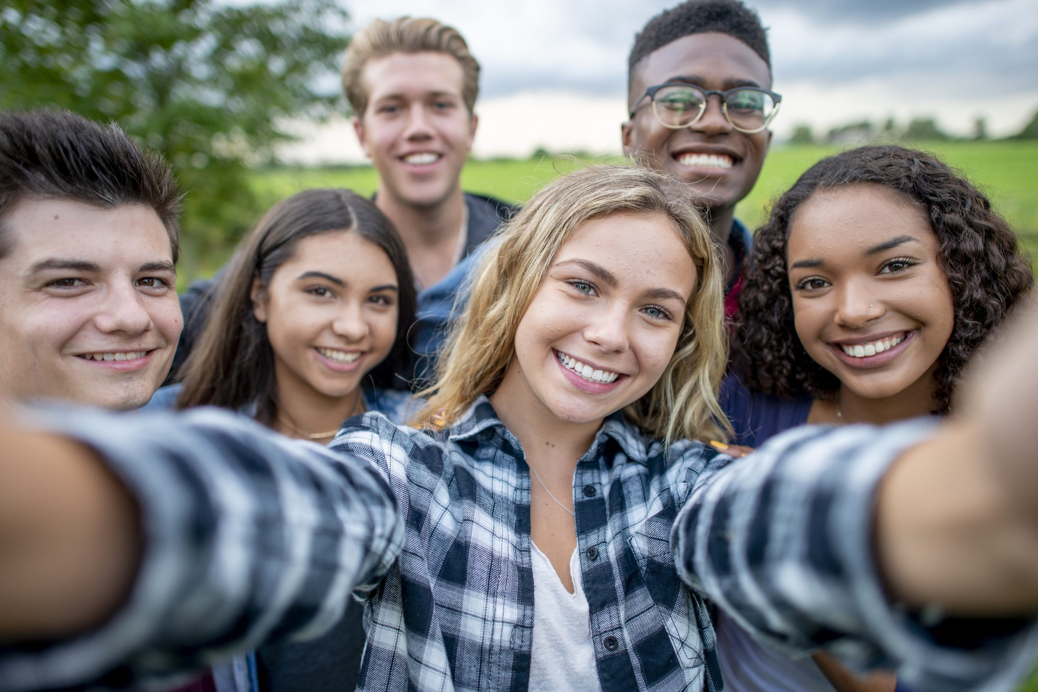 A group of multi-ethnic students taking a selfie outside.  They are dressed casually and having fun together in a group.