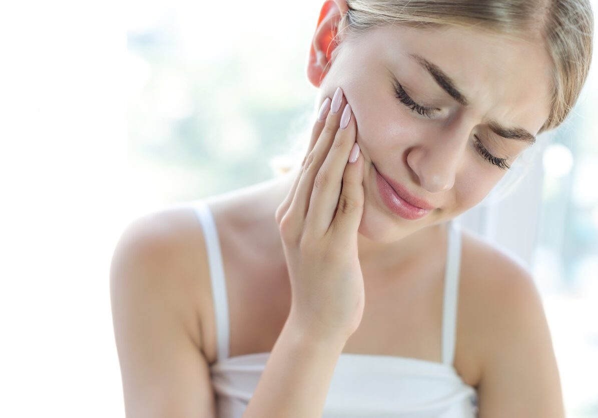 Teen girl holding side of face, indicating tooth pain