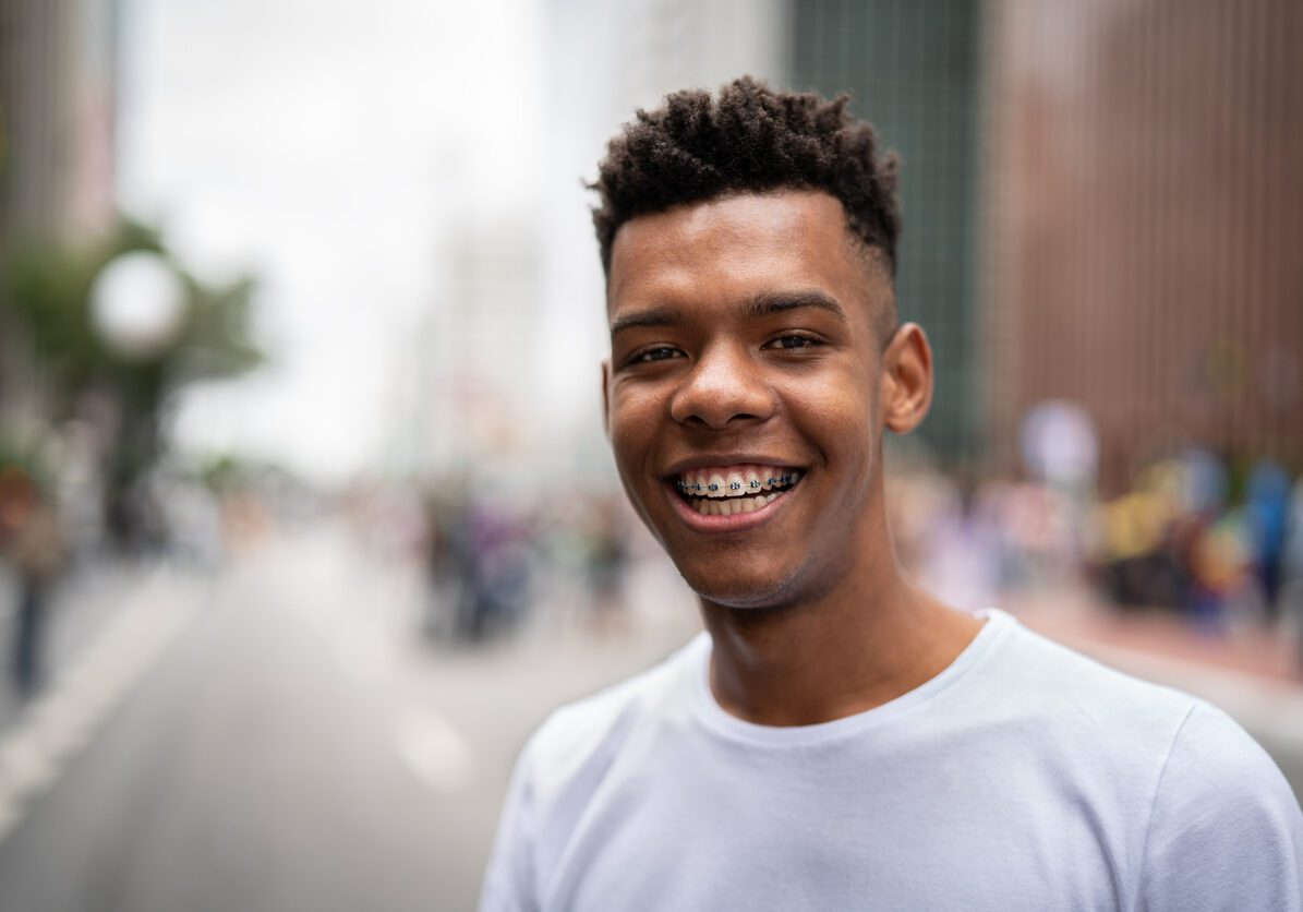 Young black man looking at camera and smiling.