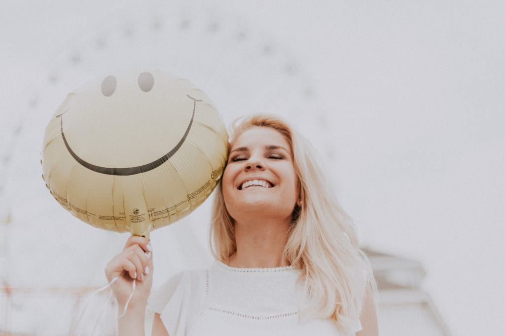 Smiling woman holding a balloon with a happy face on it.