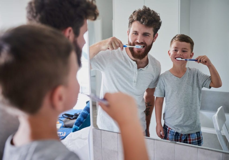 Shot of a father and his little son brushing their teeth together in the bathroom at home